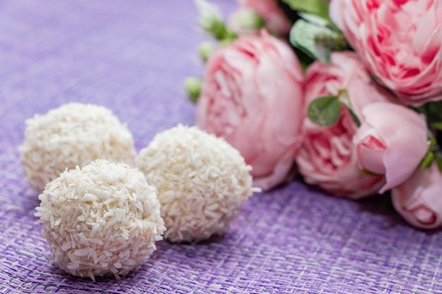 Bonbons de noix de coco maison sur fond de fleurs roses. bonbons pour la saint valentin.