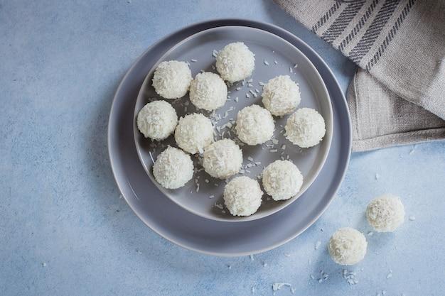 Bonbons à la noix de coco sur une plaque grise sur fond de table en béton bleu. vue de dessus, espace de copie