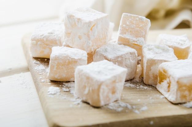 Bonbons orientaux au sucre en poudre sur une planche de bois