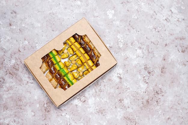 Bonbons orientaux traditionnels avec différents écrous sur fond de béton, vue de dessus, espace copie