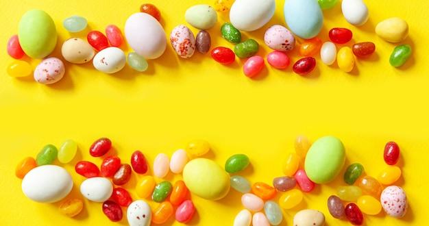 Bonbons de pâques oeufs en chocolat et bonbons jellybean isolés sur table jaune à la mode