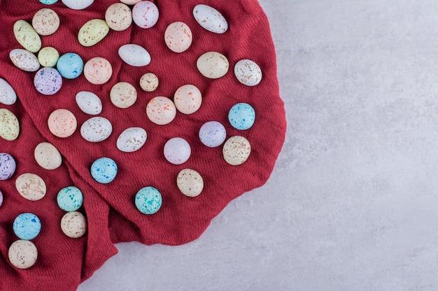 Bonbons en pierre colorés sur un morceau de nappe. photo de haute qualité