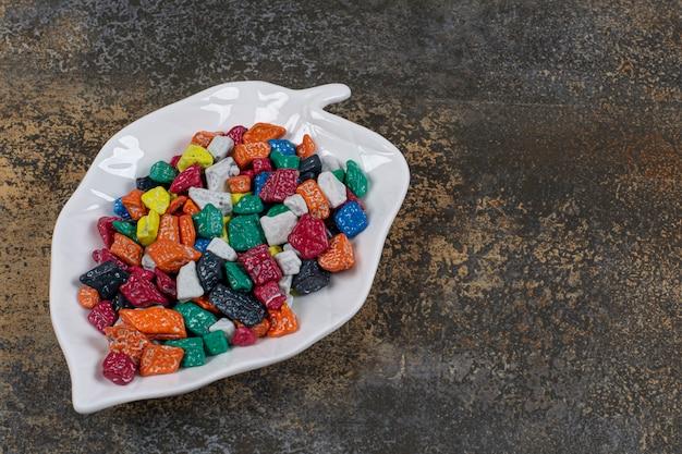 Bonbons en pierre multicolores sur plaque en forme de feuille.