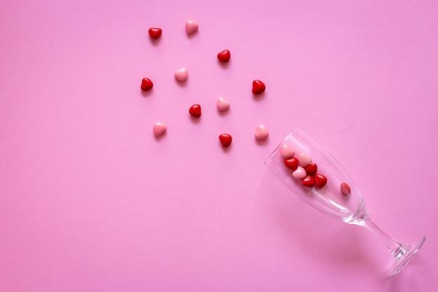 Bonbons ou pilules en forme de coeurs dans un verre à vin. concept saint valentin ou médecine, pharmacie.