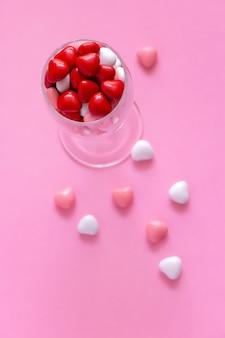 Bonbons ou pilules en forme de coeurs dans un verre à vin. concept saint valentin ou médecine.