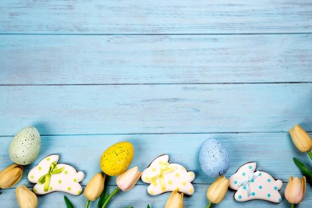Des bonbons pour fêter pâques. pain d'épice en forme de lapin de pâques, oeufs colorés et tulipes