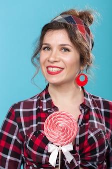 Bonbons, régime alimentaire et malbouffe concept - portrait de femme pin-up avec grosse sucette sur surface bleue