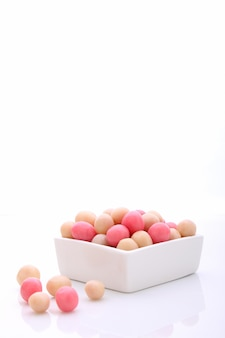 Bonbons roses et blancs dans une assiette blanche ronde sur fond blanc