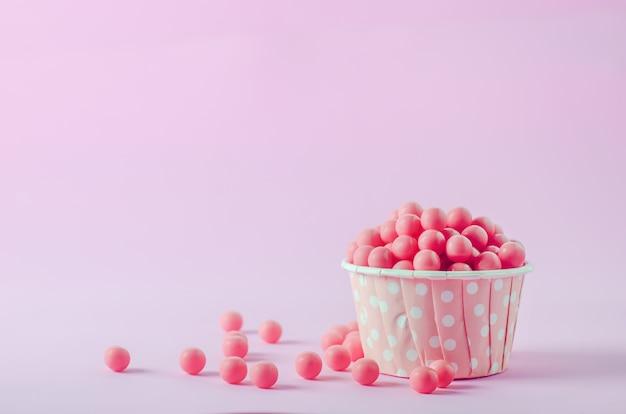 Bonbons roses dans une tasse de papier rose avec motif à pois blancs sur fond rose
