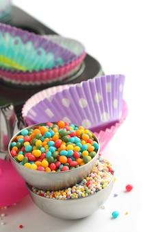 Bonbons saupoudrés avec des cas de petits gâteaux et un plat de cuisson sur blanc