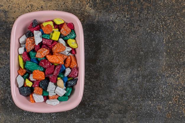 Bonbons savoureux en pierre dans un bol rose.
