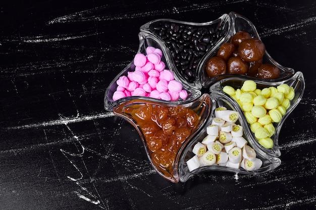 Bonbons et sortes de confitures dans des coupes en verre.