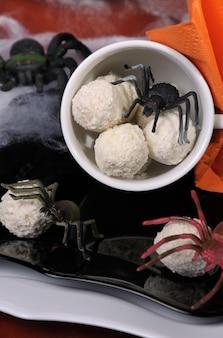 Bonbons sous forme d'œufs d'araignée dans une tasse sur la table à halloween