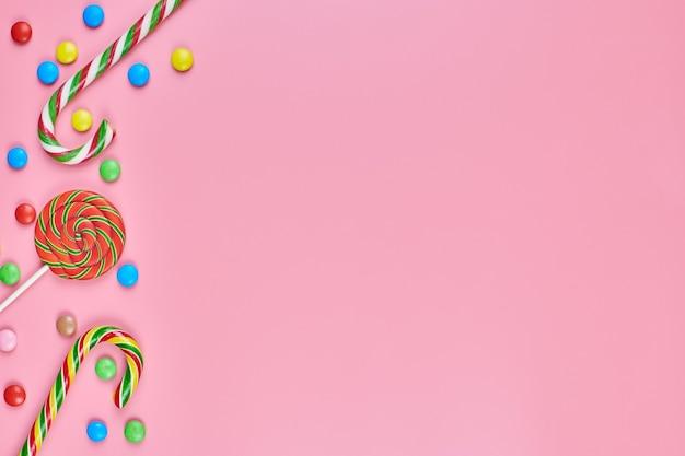 Bonbons, sucette et cannes de bonbon sur fond rose, copiez l'espace.