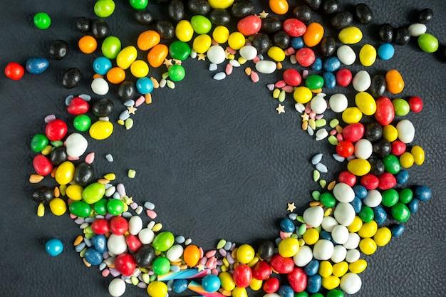 Bonbons et sucettes multicolores sur un fond sombre.