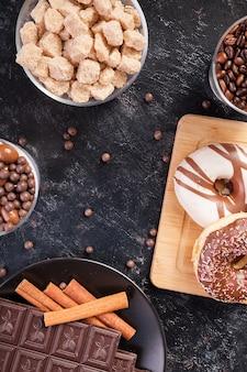 Bonbons, sucre brun, beignets et café sur fond de bois vintage foncé