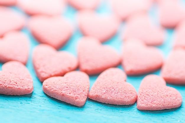 Bonbons de sucre rose saupoudrés sur fond bleu clair