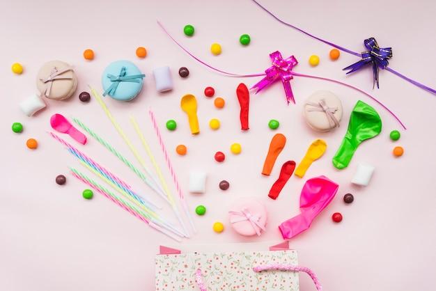 Bonbons sucrés; macaron; des ballons; et rubans sur le sac à provisions