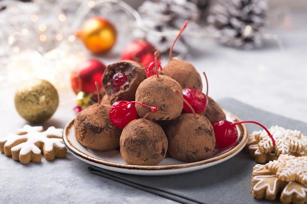 Bonbons sucrés de noël sur la table des desserts. boules de biscuit avec cerise - pop loli ou pop gâteau. décoration de nouvel an et boisson au cidre de pomme. concept de holidey heureux