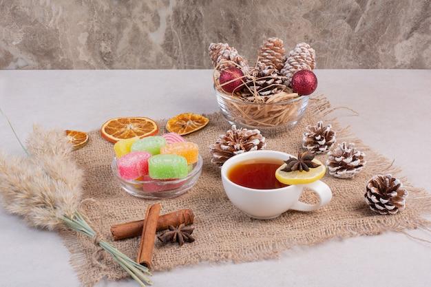 Bonbons sucrés avec une tasse de thé savoureuse sur un sac. photo de haute qualité