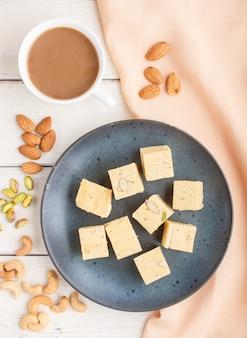 Bonbons traditionnels indiens à base de papdi dans une assiette en céramique bleue avec des amandes, un pistache et une tasse de café sur un bois blanc.