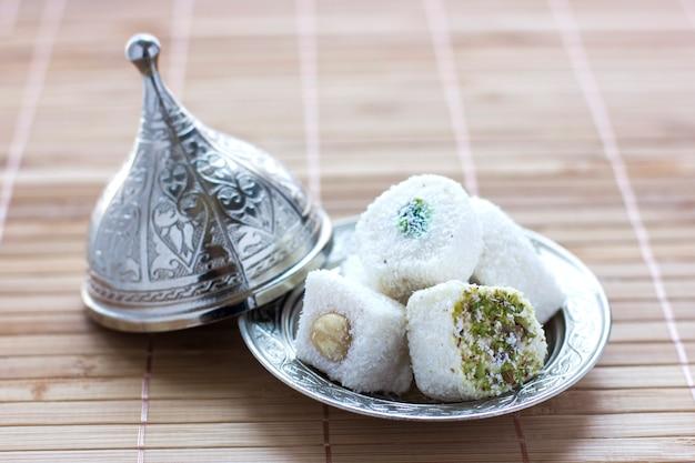 Bonbons traditionnels turcs lukum sur une soucoupe en argent avec couvercle