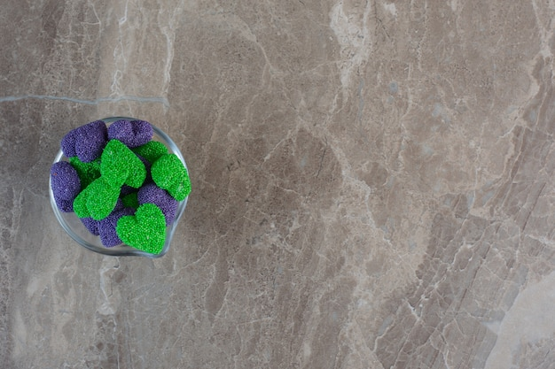 Bonbons violets et verts en forme de coeur dans un bol en verre.