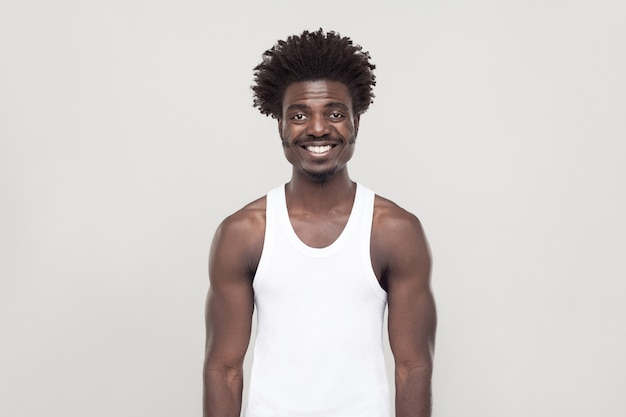 Bonheur afro homme regardant la caméra et souriant à pleines dents. prise de vue en studio. fond gris