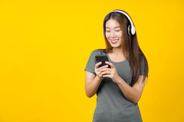 Bonheur asiatique souriante jeune femme portant des écouteurs sans fil technologiques pour écouter de la musique