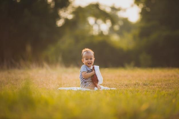 Bonheur bébé garçon assis sur l'herbe dans le champ