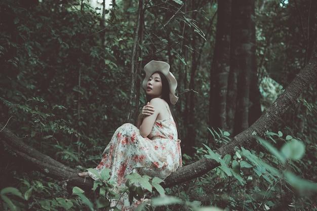 Bonheur belle femme asiatique portant un chapeau de paille dans le parc