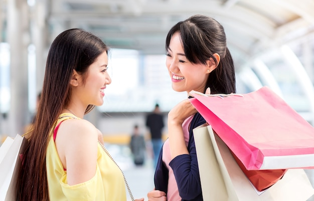 Bonheur couple femme, amie, souriez pendant le shopping de mode ensemble près du magasin de vente de mode.