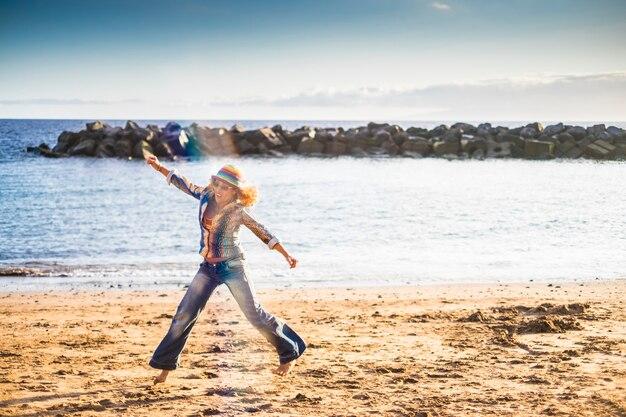 Bonheur et feedom dans le concept de vacances avec une belle femme bouclée d'âge moyen sautant à la plage en profitant de l'activité de plein air de loisirs dans la nature avec la mer bleue