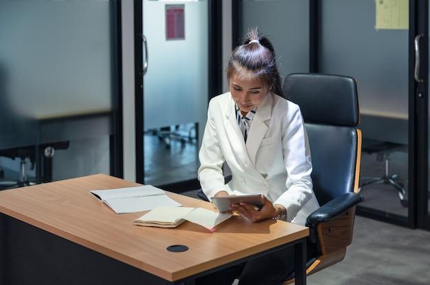 Bonheur de femme jeune gestionnaire asiatique travaillant avec tablette sur le bureau au bureau