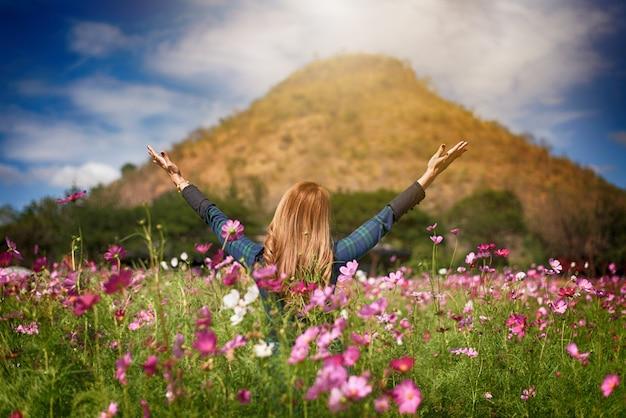 Bonheur femme reste en plein air dans un jardin fleuri sous le soleil