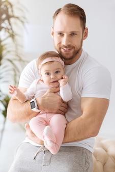 Le bonheur de la paternité. joyeuse petite fille concentrée mignonne se trouvant dans les mains du jeune père et regardant ailleurs tout en exprimant la positivité