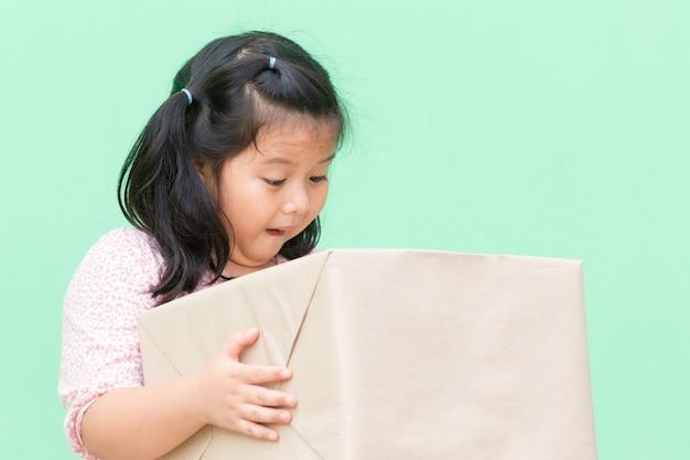 Bonheur de petit garçon avec boîte-cadeau de colis brun