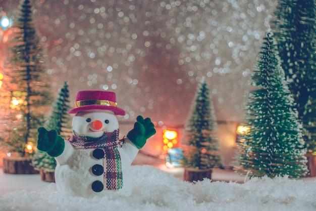 Bonhomme de neige avec arbre de noël et ornement. fond de paillettes.