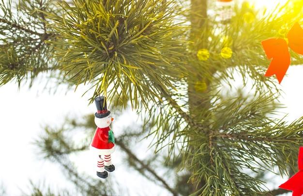 Bonhomme de neige et arcs rouges sont accrochés au pin de noël. photo naturelle dans la forêt gelée. carte postale de joyeuses fêtes. décoration d'ornements du nouvel an. temps de neige.