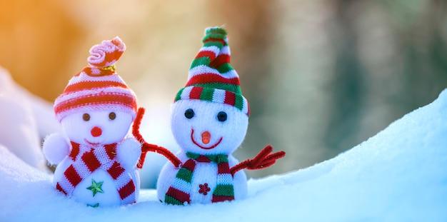 Bonhomme de neige bébé de deux petits jouets drôles en chapeaux tricotés et écharpes dans la neige profonde