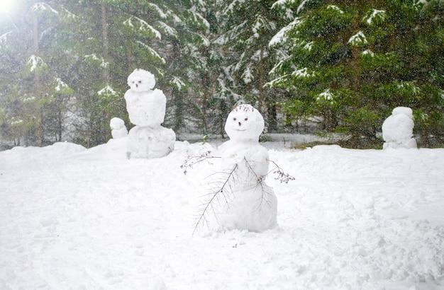 Bonhomme de neige coincé ensemble dans la forêt sourire bonhommes de neige de la famille hiver froid wallpaper