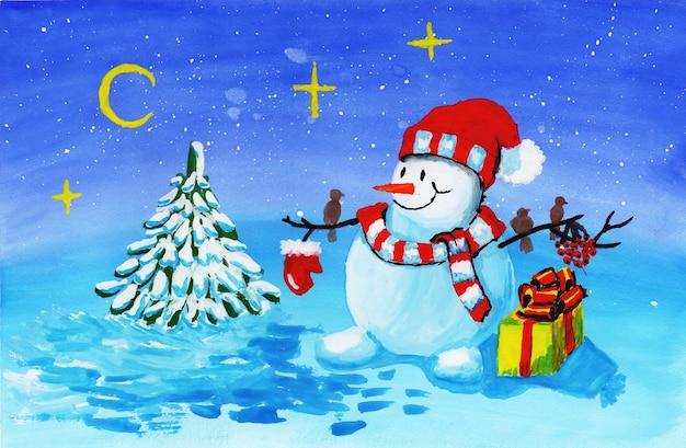 Un bonhomme de neige dans un chapeau rouge et une écharpe rayée se tient près d'un arbre de noël avec une boîte-cadeau jaune