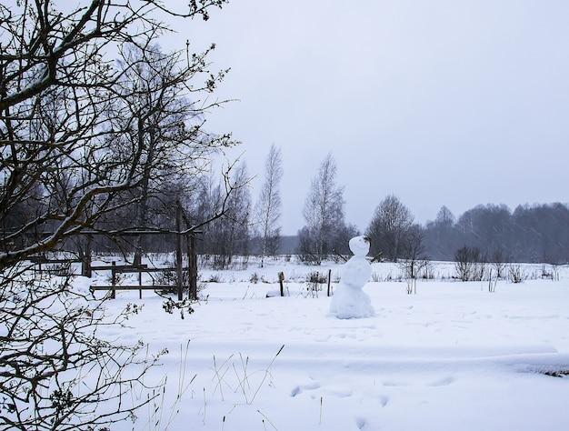Bonhomme de neige drôle fait par des enfants sur le champ rural couvert de neige