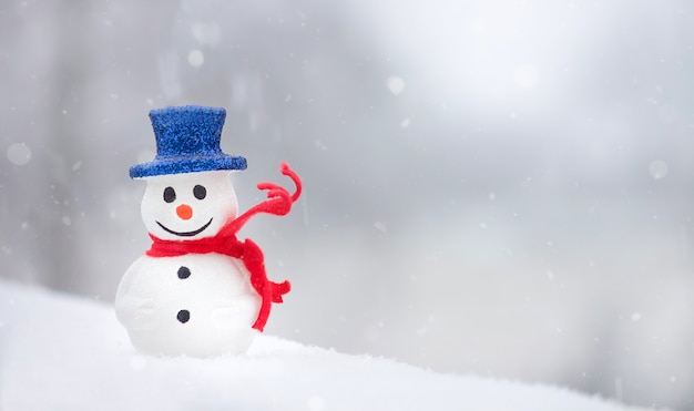 Bonhomme de neige avec écharpe rouge sur fond de neige blanche vacances d'hiver temps de noël copy space