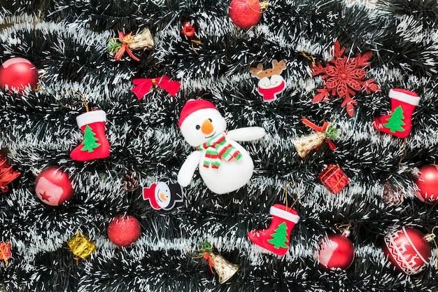 Bonhomme de neige entre jouets de noël sur des guirlandes
