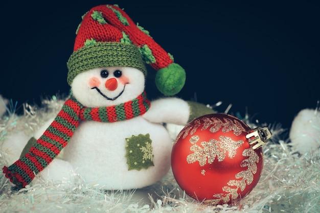 Bonhomme de neige jouet avec boule rouge festive sur fond noir.photo avec une copie de l'espace