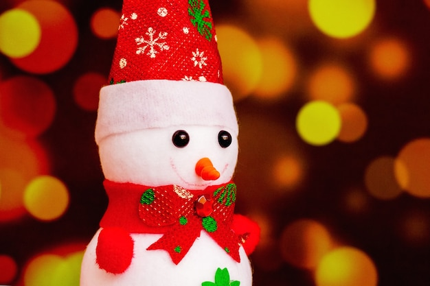 Bonhomme de neige jouet sur un fond rouge flou avec bokeh. fêter noël et le nouvel an_