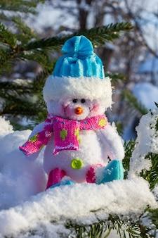 Bonhomme de neige jouet de noël dans un bonnet bleu assis sur la neige sur les branches de l'arbre de noël se bouchent