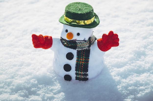 Bonhomme de neige se tenir parmi des tas de neige dans le parc. le soleil se réchauffe mais il fait froid à hokkaido, au japon.