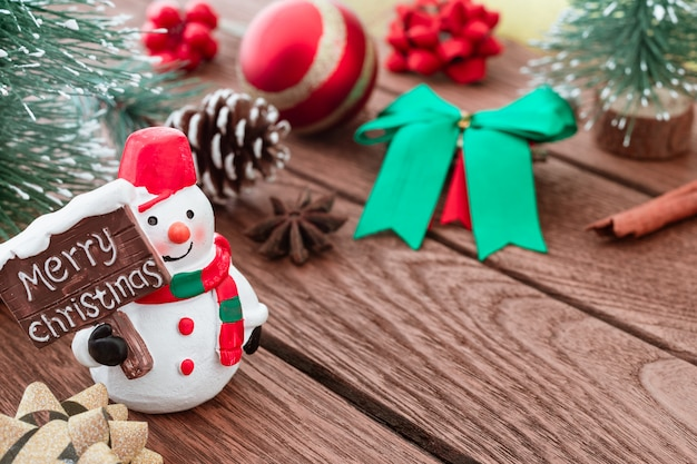 Bonhomme de neige avec signe joyeux noël et ornamets de noël sur bois